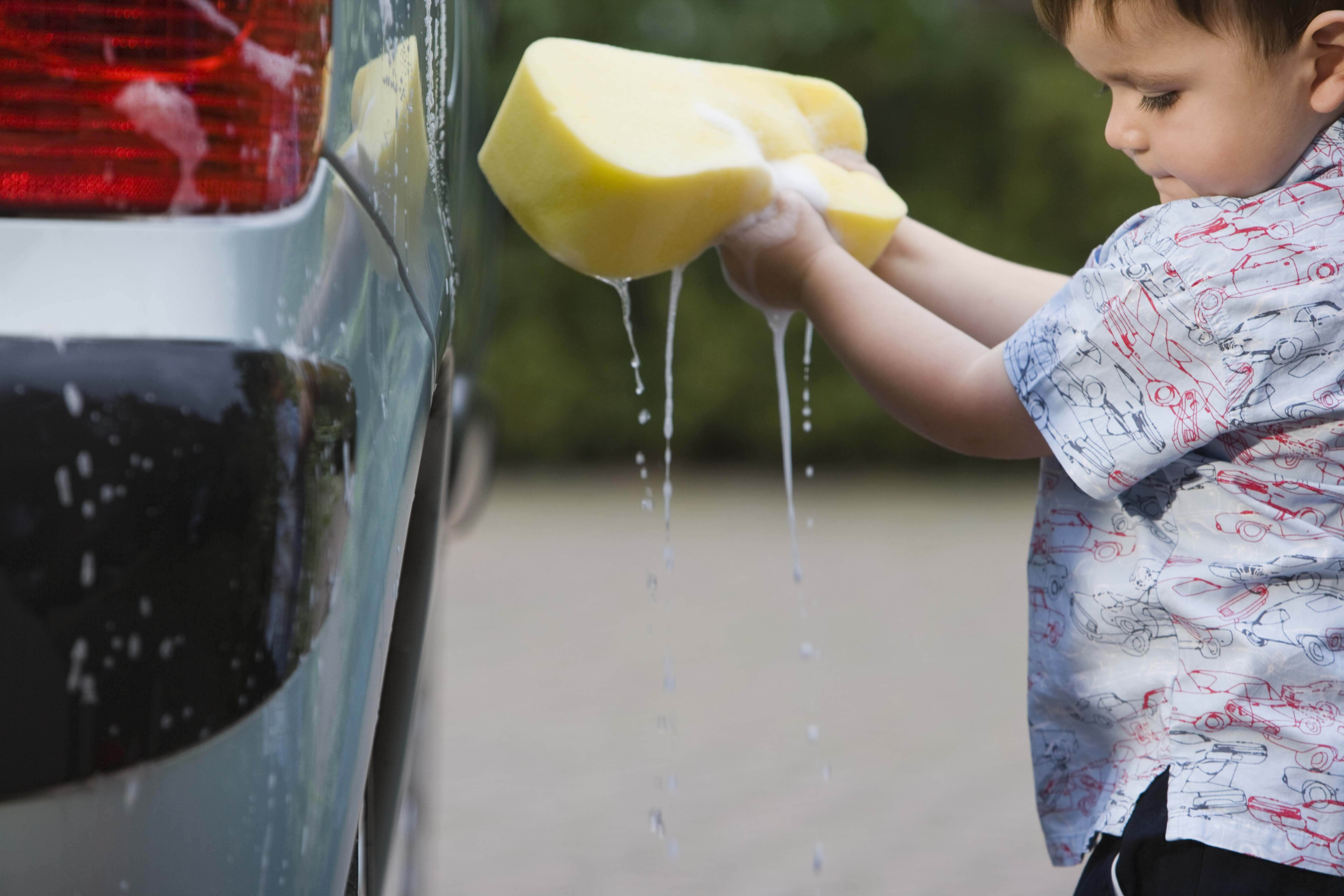 A young boy cleaning a car with a foam sponge