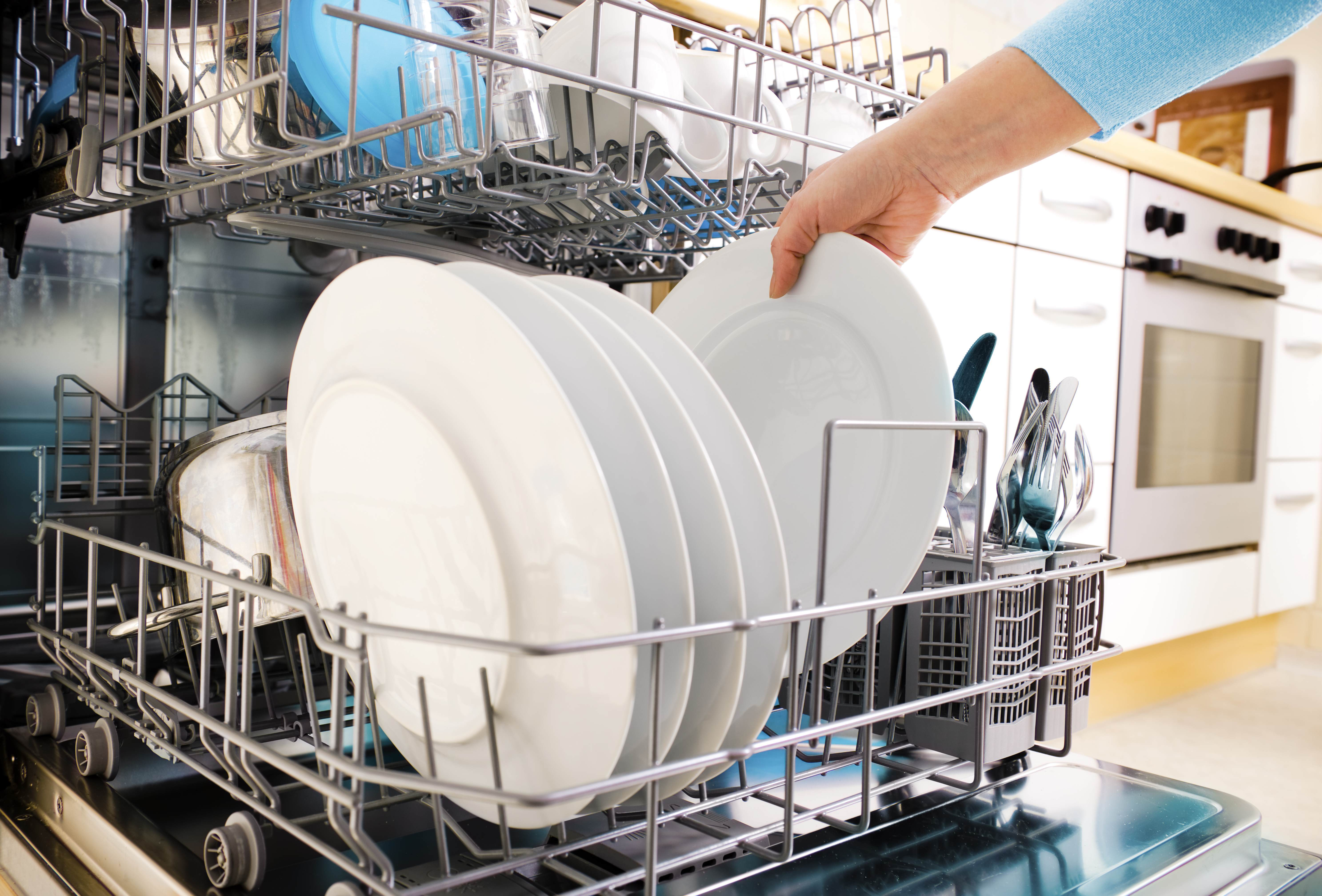 Clean plates being unloaded from a dishwasher