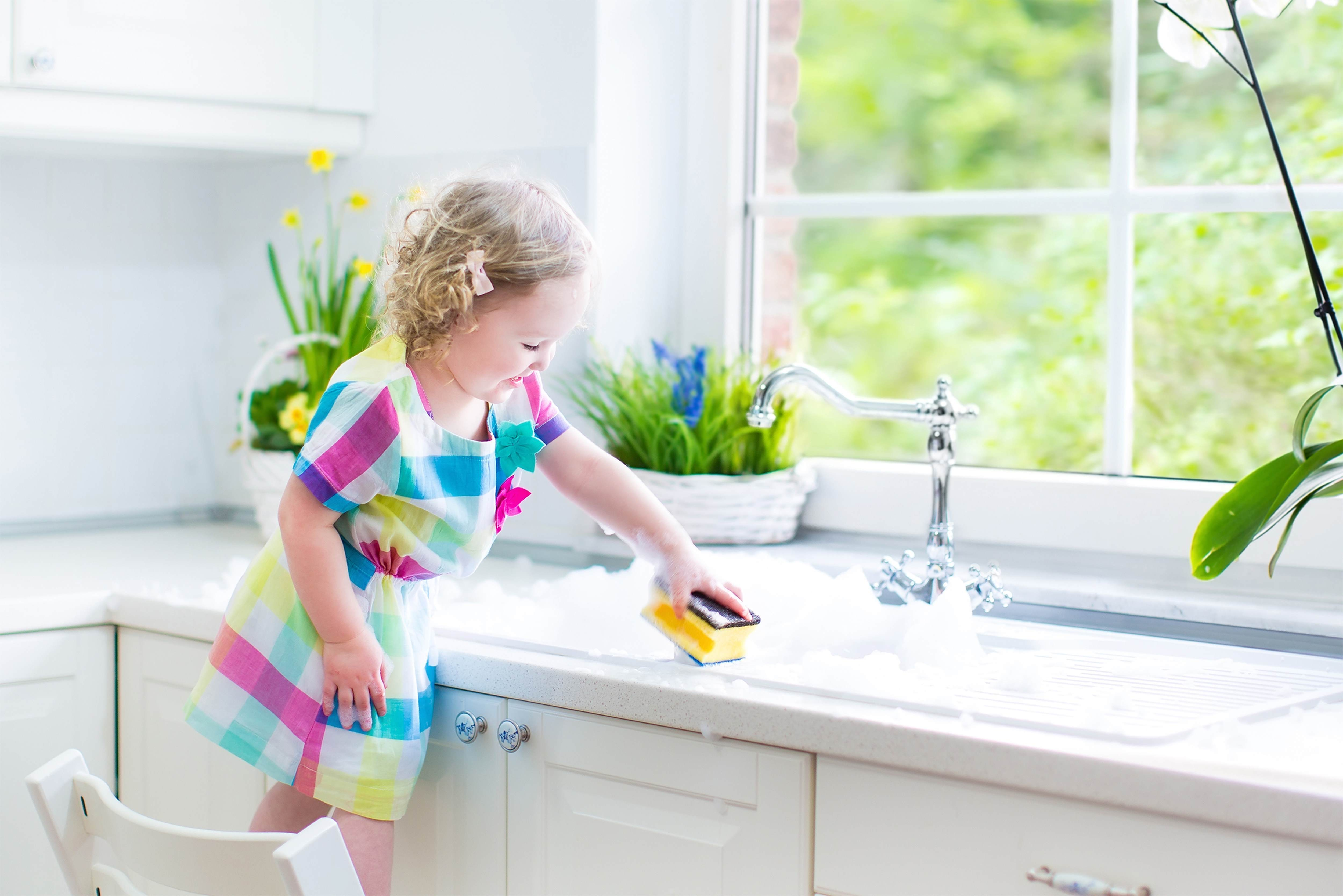 A little girl stood on a chair washing up crockery in a sink