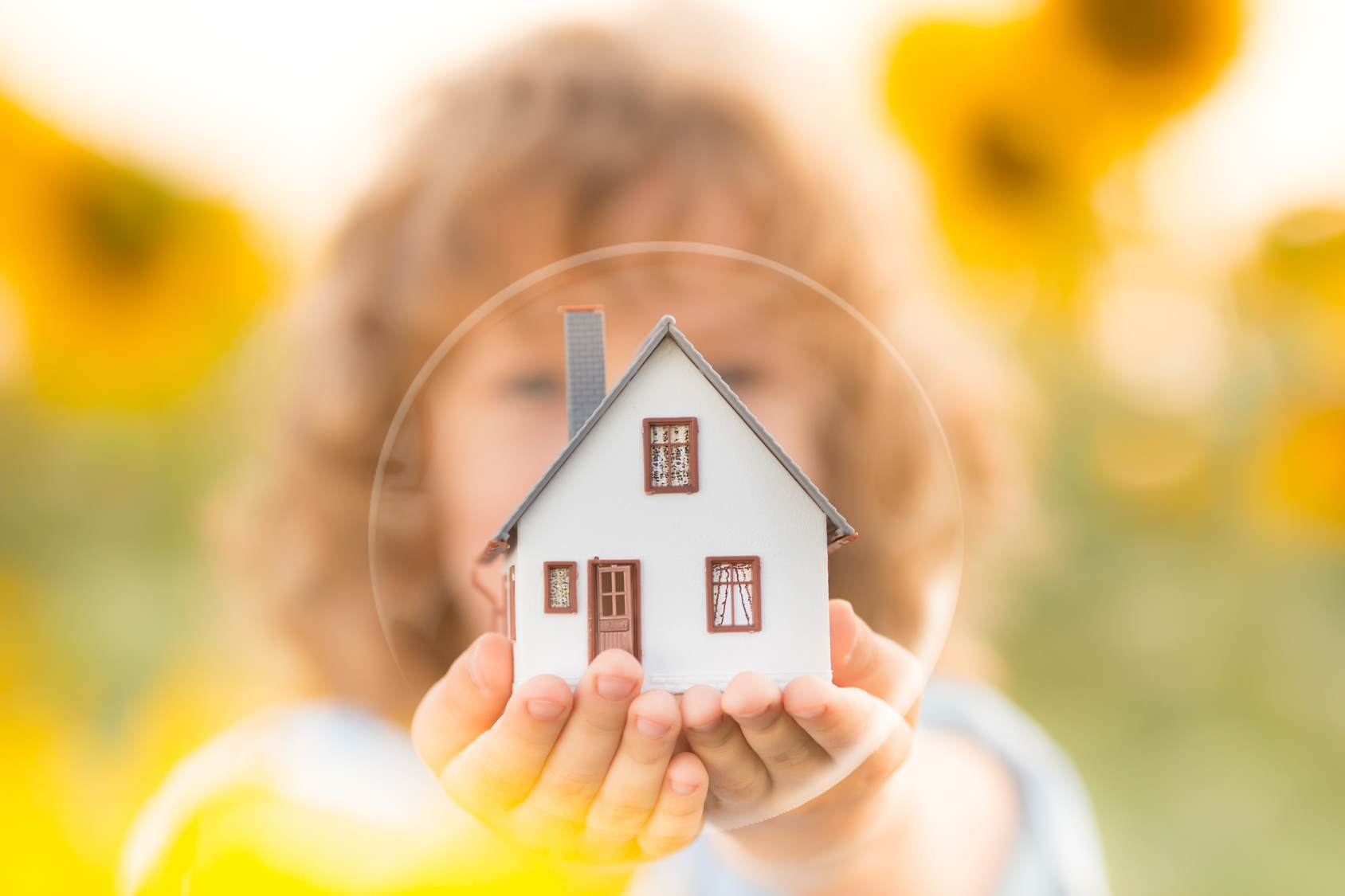 A child holding a miniature house in the palms of both hands