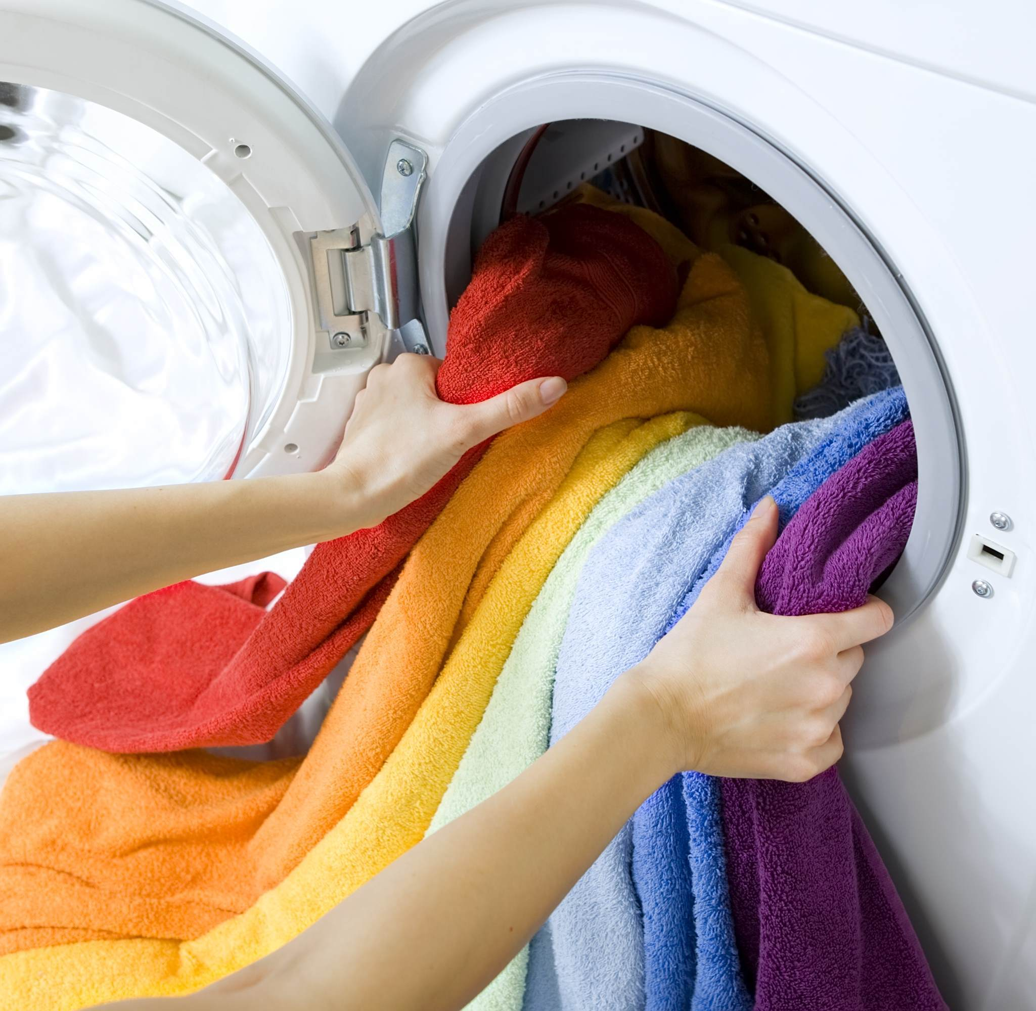 Clean towels being removed from a washing machine
