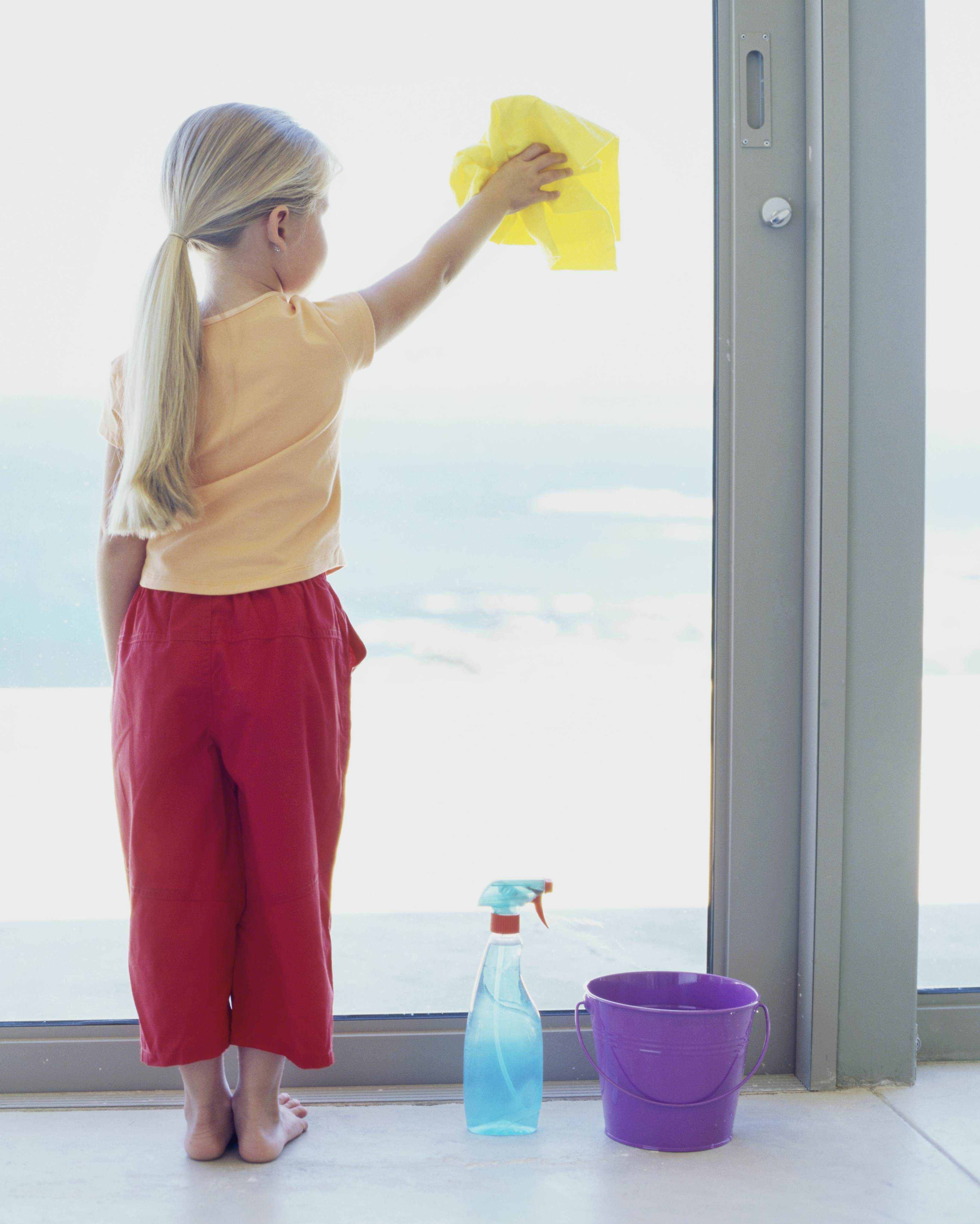 A young girl washing windows