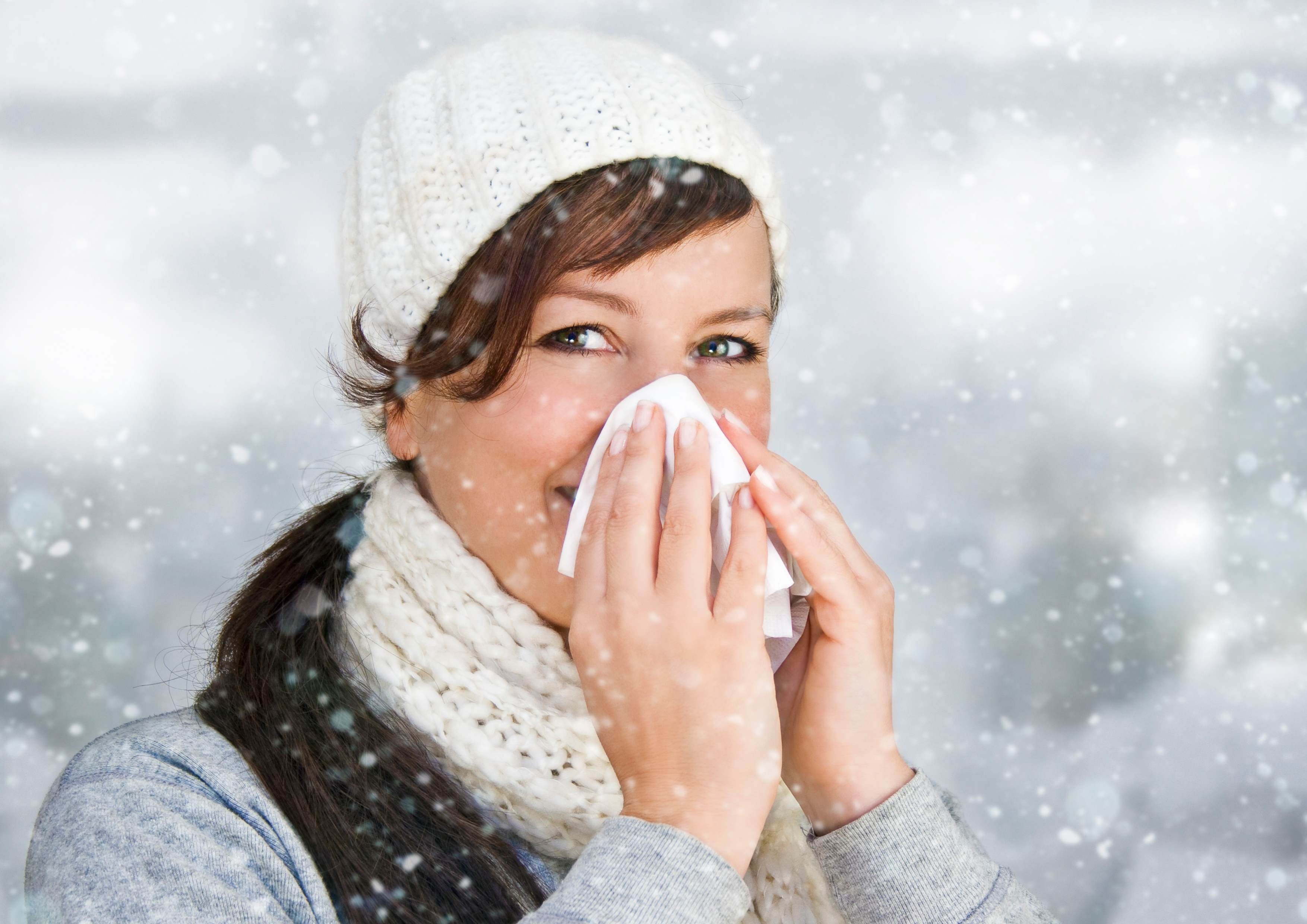 A woman blowing her nose outside in the snow